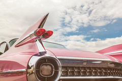 Rear end of a pink classic car. Retro styled image of the rear end of a pink classic car Royalty Free Stock Photos