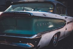Rear end of a worn and beat up classic American car from the fifties. Partial rear close up of an old untouched and not restored classic car from 1958 royalty free stock images