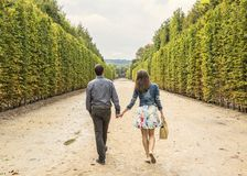 Couple Walking in a Garden. Rear image of a young couple walking hand in hand in a park in autumn Royalty Free Stock Photography