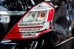 A rear lamp damaged in the incident. A rear lamp damaged in the incident and a fender of a car, a close-up rear light of a black car stock photography