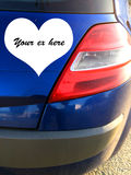Rear light cluster on car with heart shaped space. Closeup of rear light cluster on off side of blue saloon car  with white heart shape superposed on the boot Stock Images