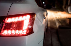 Rear light of white car. At night. Break light and head light are active Royalty Free Stock Image