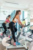 Fit women burning calories during indoor cycling class in a mode Royalty Free Stock Photos