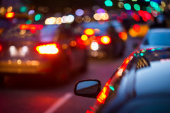 Rear mirror of a car parked next to road with busy traffic. Blurred background Royalty Free Stock Image