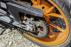 Rear orange wheel and chain of sport bike. Close up shot Royalty Free Stock Images