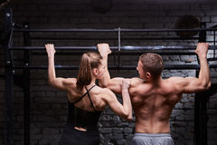 Rear photo of young attractive caucasian crossfit man and woman while working out in gym Royalty Free Stock Photo