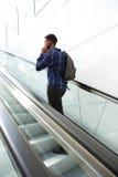 Rear portrait of man standing on escalator talking on smart phone Royalty Free Stock Image