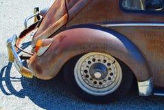Rear quarter of rusty old car on sunny street Royalty Free Stock Photos