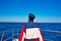 Rear sailor cap man sailing sea ocean in a boat Royalty Free Stock Image