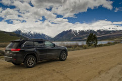 Rear shot of black Jeep Gran Cherokee around snow. Rear/side shot of black Jeep Grand Cherokee with blue lakes and snowy peaks in the background royalty free stock image