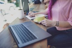 Woman typing on notebook with blank screen, sitting at wooden ta royalty free stock photo