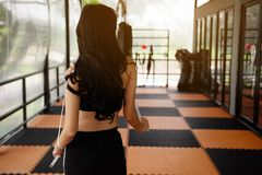 Rear shot of long hair girl at fitness. Rear shot of Asian long hair slim woman, 20-30 years old, holding tape measure and looking at fitness equipments at stock images
