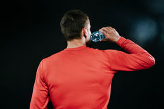 Rear shot portrait of handsome muscular Caucasian jogger wearing red sportswear drinking water, relaxing after intense physical tr. Caucasian sportsman wearing Stock Image