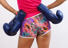 Rear shot of pretty woman wearing blue boxing gloves. Seductive Asian woman wearing shorts, pink tank top, isolated on white background Stock Photography