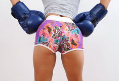 Rear shot of pretty woman wearing blue boxing gloves. Rear view of attractive woman wearing shorts and blue boxing gloves Stock Photography