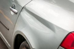 Rear side of broken and damaged silver car wreck in crash accident with scratched paint in collision close up.  stock photo