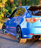 Rear side view of blue sport car Stock Images