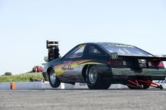 Drag car. Rear side view of Chrysler drag car making a wheelie on the track during the john scotti all out, august 20 2016 Royalty Free Stock Images