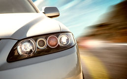 Rear side view of a sport car in blurred motion. A car driving on a motorway at high speeds, overtaking other cars Stock Photos