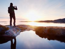 Rear silhouette of travelling man taking selfie at sea. Tourist with backpack standing on a rock. Looking  over blue sea and taking photo by his smart phone Stock Photos