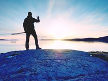 Rear silhouette of travelling man taking selfie at sea. Tourist with backpack standing on a rock. Looking  over blue sea and taking photo by his smart phone Stock Photography