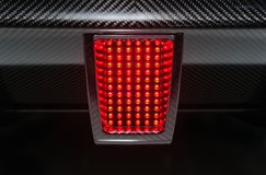 Rear sport car light. Rear light of powerful modern sport car with carbon bumper. Active red stop signal mode Stock Images