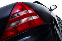 Rear tail light assembly on a modern car. Close up low angle view of the red rear tail light assembly on a modern black car showing lens detail isolated on white Stock Image