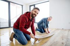 A mature man with his senior father laying vinyl flooring, a new home concept. A rear and top view of mature men with his senior father laying vinyl flooring, a stock photography
