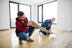 A mature man with his senior father laying vinyl flooring, a new home concept. A rear and top view of mature men with his senior father laying vinyl flooring, a stock photo