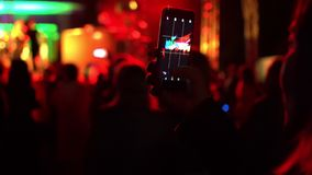 Rear video shot of young woman making video recording of summer festival concert using smartphone in crowd of people. Multicolored blurred background from stock footage