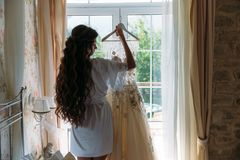 Rear viev bride in lingerie in the morning before the wedding. White negligee of the bride, preparing for the wedding. Ceremony. girl with long hair holding her Stock Photo