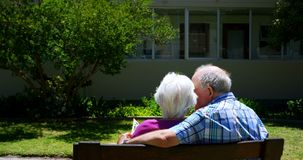 Rear view of active Caucasian senior couple looking at photo album in the garden of nursing home 4k. Rear view of active Caucasian senior couple looking at photo stock video