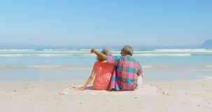 Rear view of active senior African American couple relaxing on blanket in the sunshine at beach 4k. Rear view of active senior African American couple relaxing stock video footage