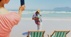Rear view of active senior African American woman taking photo of man with mobile phone at beach 4k. Rear view of active senior African American woman taking stock video footage