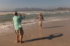 Senior man clicking photo of senior woman on the beach. Rear view of active senior men clicking photo of senior women on the beach royalty free stock photo