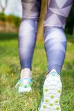 Rear view of active woman running sport shoes Stock Image