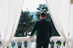 Rear view of adult male businessman in a classic black suit with a white shirt and a bow tie. Portrait of the groom. Waiting for the bride on a wedding day in Stock Image