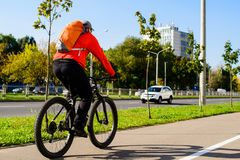 Rear view of adult man with backpack riding a bicycle in the cit. Y street. Car free day, healthy lifestyle concept Stock Image