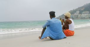 Rear view of African american couple drinking pineapple juice on the beach 4k stock footage