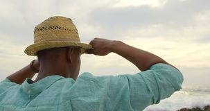 Rear view of African American man in hat standing on the beach 4k. Rear view of African American man in hat standing on the beach. He is looking away 4k stock video