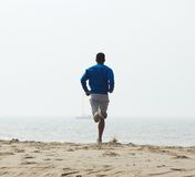 Rear view african american man jogging. At the beach Stock Image