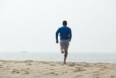 Rear view african american man running. On the beach Royalty Free Stock Photography