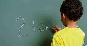 Rear view of African American schoolboy solving math problem on chalkboard in classroom at school 4k. Rear view of African American schoolboy solving math stock video