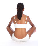 Rear view african american woman sits cross legged. Rear view of a beautiful healthy young african american woman wearing white sports underwear, sitting cross Stock Image