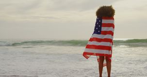 Rear view of African American woman wrapped in American flag on the beach 4k. Rear view of African American woman wrapped in American flag on the beach. She is stock footage