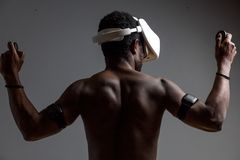 Backside of African male muscular athlet with naked torso using vr headset royalty free stock image