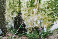 Rear view of an aged angler sitting on the river bank. Rear view of a professional retired fisher holding a rod while sitting on the riverbank royalty free stock photos