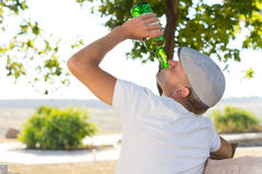 Rear view of an alcoholic man drinking in the park Stock Images