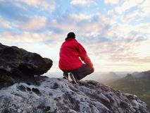 Rear view of alone hiker in dark red outdoor clothes sitting on rock. Sharp rocky peak  above mountains valley, cold Sun hidden in rainy clouds Stock Photo