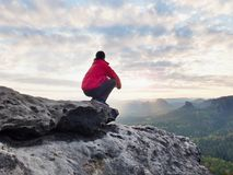 F alone hiker in dark red outdoor clothes sitting on rock. Sharp rocky peak. Rear view of alone hiker in dark red outdoor clothes sitting on rock. Sharp rocky Royalty Free Stock Image
